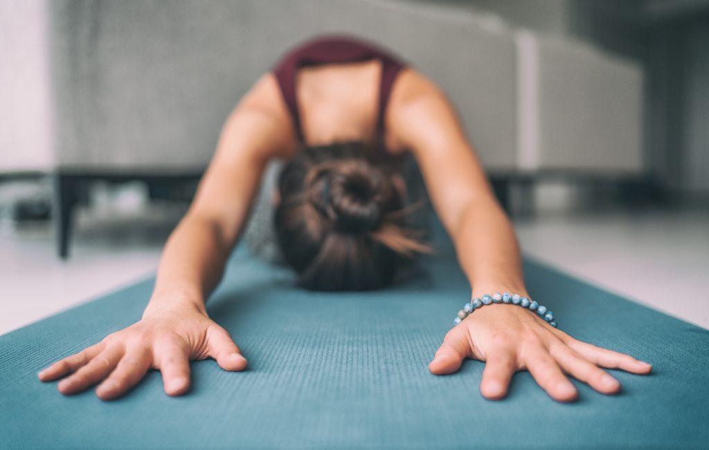 Lady doing yoga pose on yoga mat
