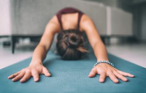 Lady doing yoga pose on yoga mat
